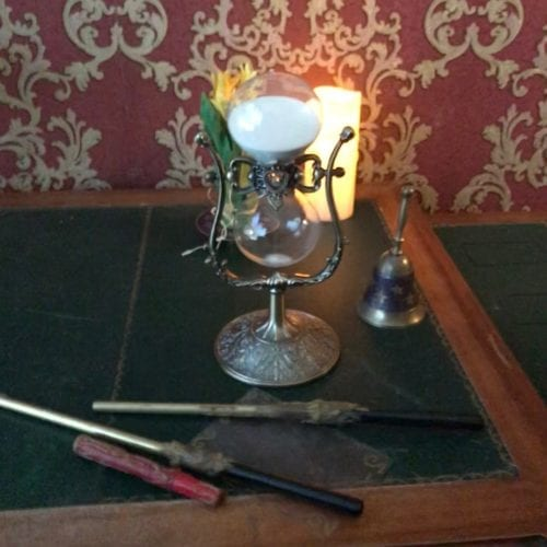 Un bureau avec des baguettes de magicien et un sablier